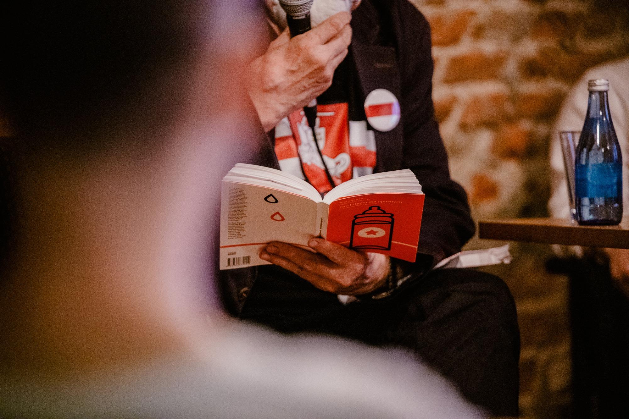 [Zdjęcie ze spotkania autorskiego. Zbliżenie na dłonie mężczyzny trzymające mikrofon przy ustach oraz książkę z czerwono-białą okładką. Mężczyzna ubrany jest na ciemno oraz ma przypiętą do ubrania przypinkę biało-czerwono-białej flagi Białorusi. Obok widać kawałek stolika ze stojącą na nim wodą i szklanką.]