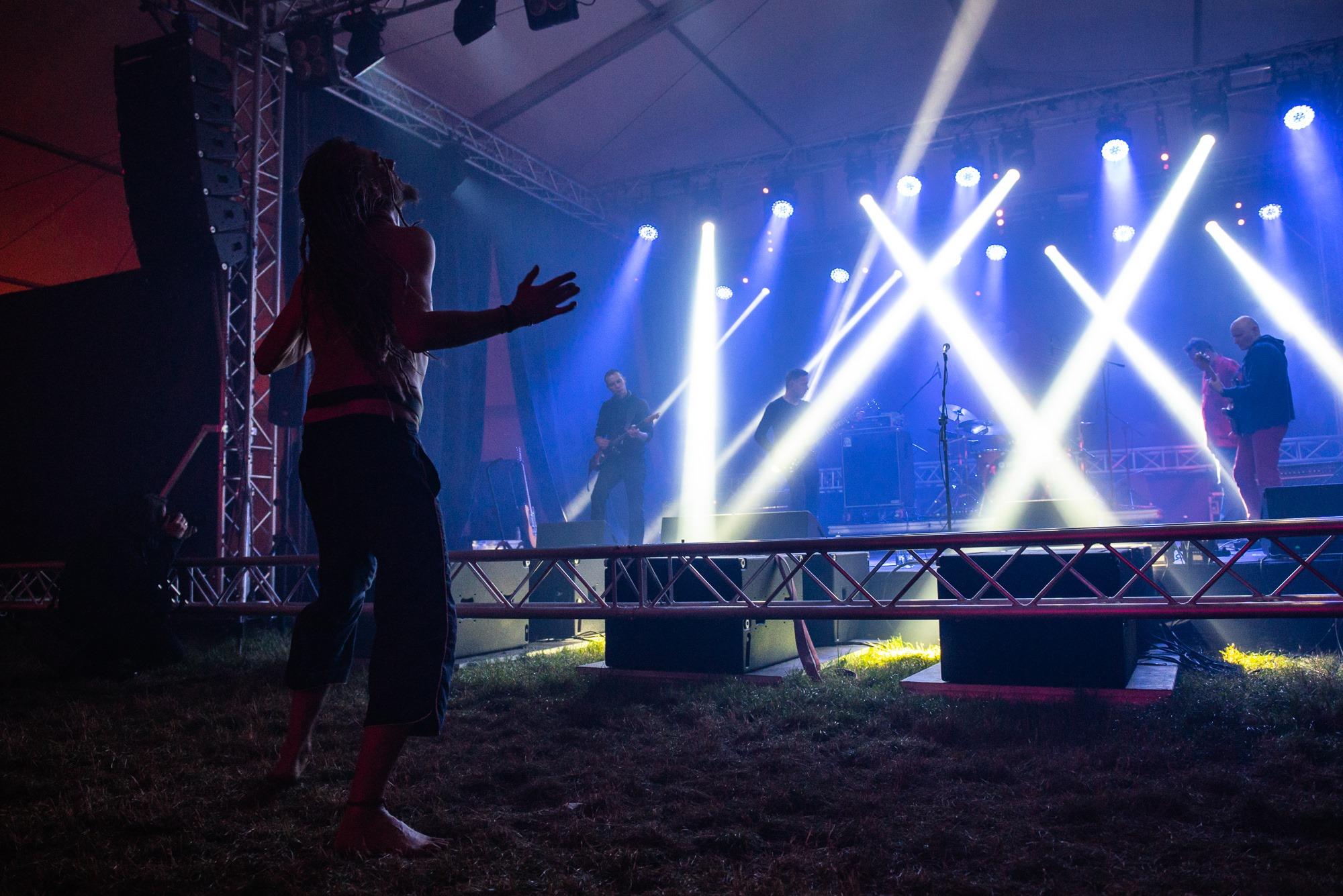 [Zdjęcie z koncertu zespołu Bielizna. Na trawie, przed sceną tańczy mężczyzna. Jego głowa jest uniesiona do góry, ręce ma zgięte w łokciach i uniesione do góry. Tańczy na boso. W tle widać scenę i zespół muzyków - trzech mężczyzn grających na gitarach oraz mężczyznę stojącego za nimi. Oświetlenie jest niebieskie.]