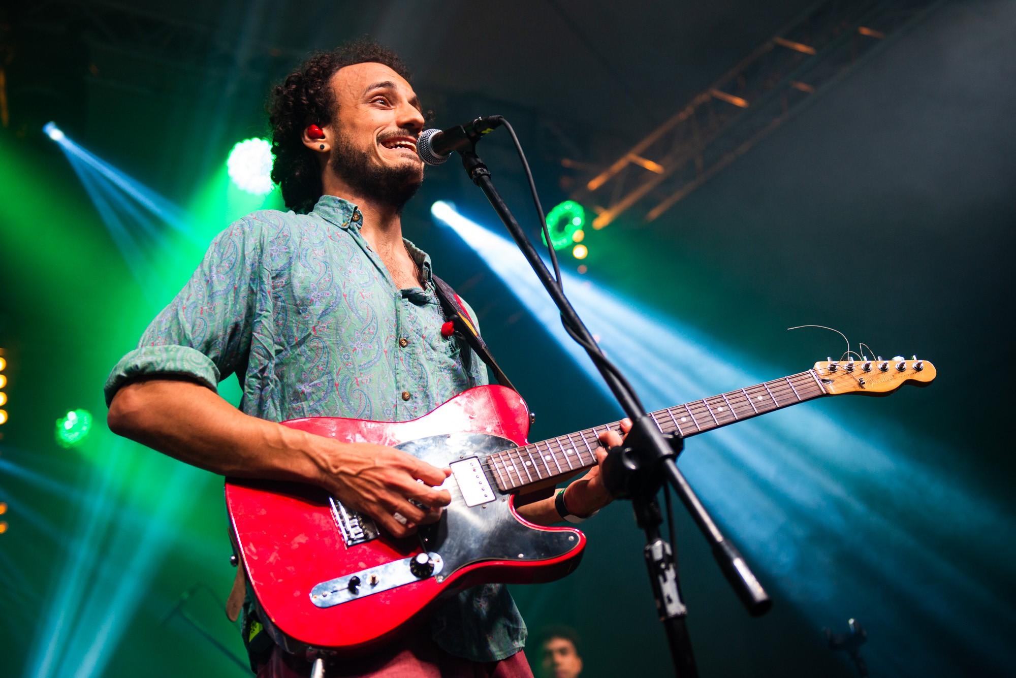 [Zdjęcie z koncertu. Mężczyzna śpiewa do mikrofonu umieszczonego na statywie i jednocześnie gra na gitarze. Jest ubrany w niebieską koszulę, ma loki i czerwoną słuchawkę w uchu. W tle widać konstrukcję scenografii. Oświetlony jest niebiesko-zielonym światłem.]