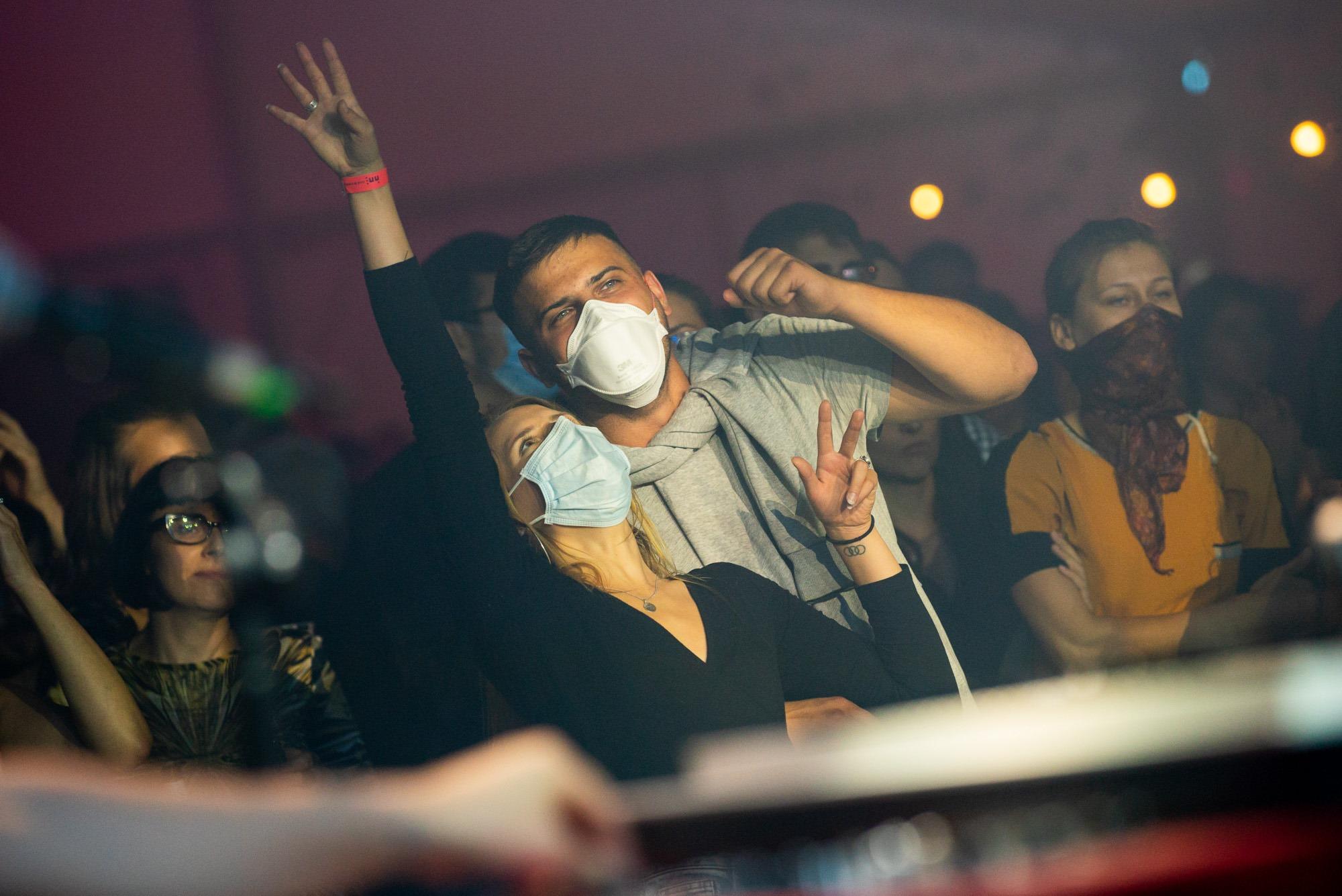 [Zdjęcie z koncertu przedstawia publiczność wpatrzoną w występujących na scenie artystów. Na pierwszym planie mężczyzna z kobietą. Ich ręce są uniesione w górę, na nosie i ustach mają założone maseczki. W tle widoczne sylwetki innych odbiorców koncertu - kobiet i mężczyzn.]