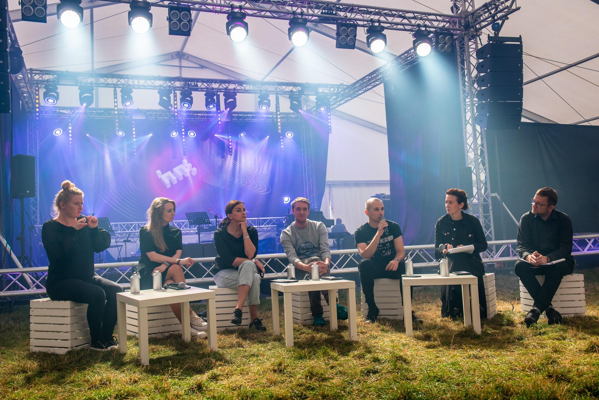 [Zdjęcie przedstawia grupę ludzi siedzących obok siebie w półokregu na białych skrzynkach, na trawie - cztery kobiety i trzech mężczyzn. Przed nimi ustawione są białe stoliki. W tle widoczna jest scena z logo festiwalu Wschód Kultury - Inne Brzmienia. Światła zamieszczone na metalowej konstrukcji skierowane są w stronę siedzących. Jeden z mężczyzn wypowiada się do mikrofonu, jedna z kobiet tłumaczy jego wypowiedź na język migowy. Reszta osób słucha z zainteresowaniem.]