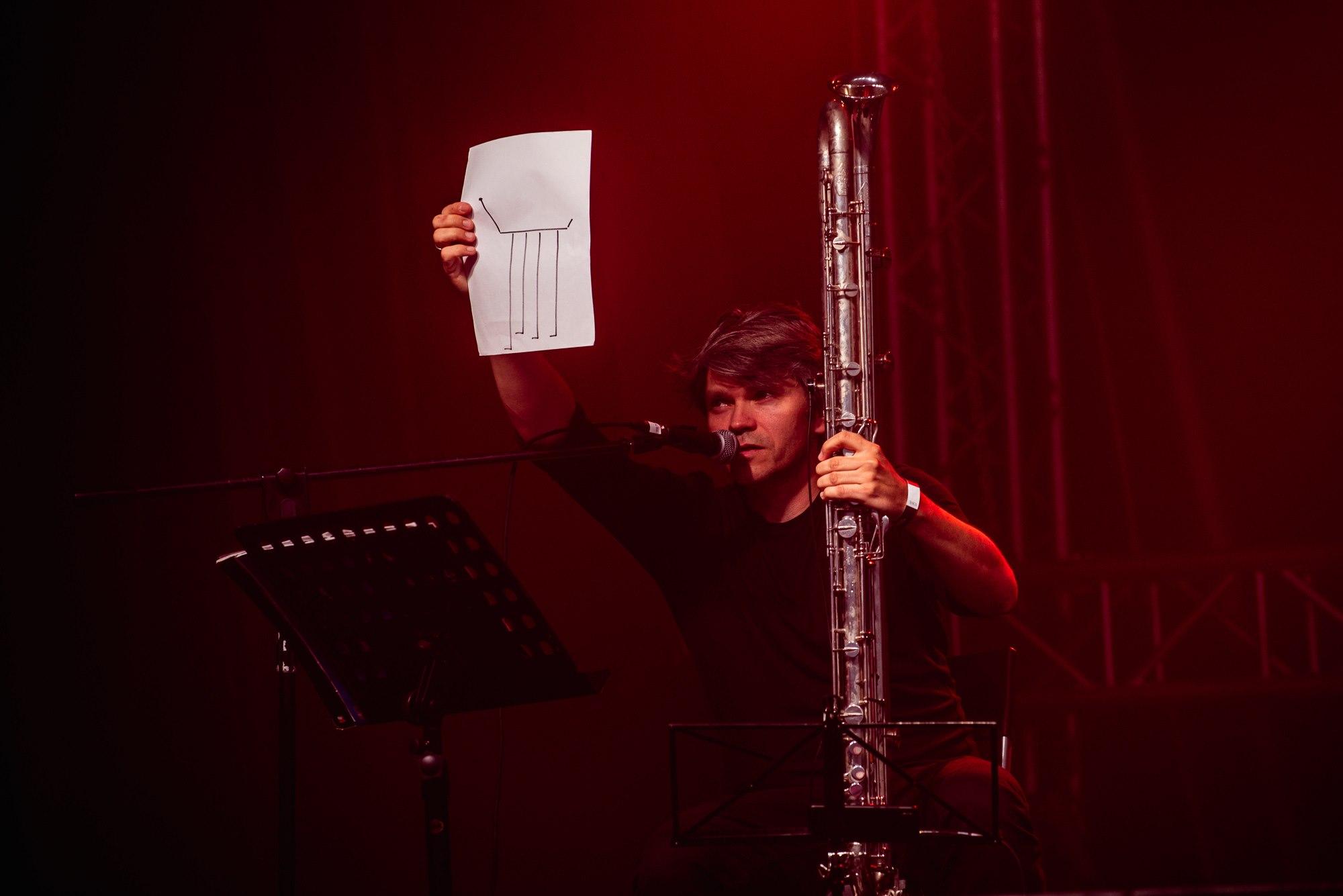 fot. Robert Grablewski [Zdjęcie muzyka oświetlonego czerwonym światłem. Muzyk podnosi w górę rękę, w której trzyma kartkę papieru]