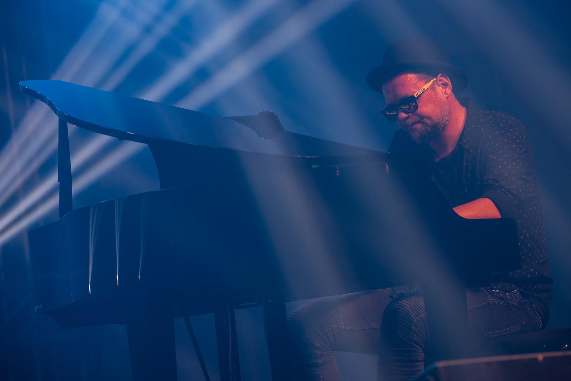 [Zdjęcie z koncertu przedstawia mężczyznę grającego na fortepianie. Mężczyzna ma ciemne okulary oraz czarny kapelusz na głowie. Ubrany jest w ciemną koszulę oraz spodnie. Oświetla go niebieskie światło.]