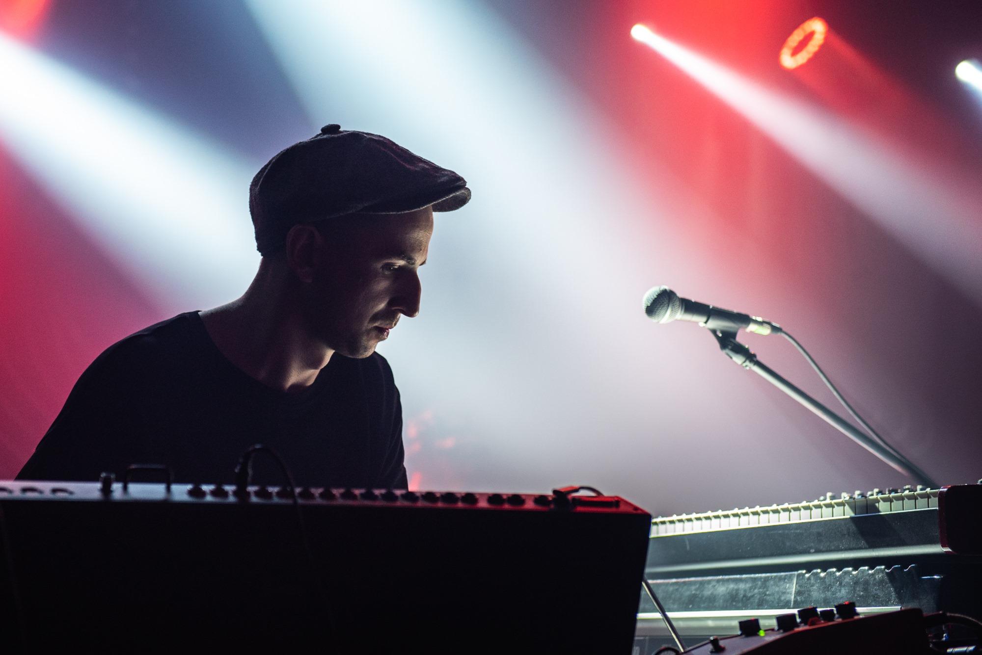 [Zdjęcie z koncertu przedstawia mężczyznę w czapce z daszkiem i ciemnej koszuli, który spogląda w dół na sprzęt muzyczny. Obok niego stoi mikrofon umieszczony na statywie.]