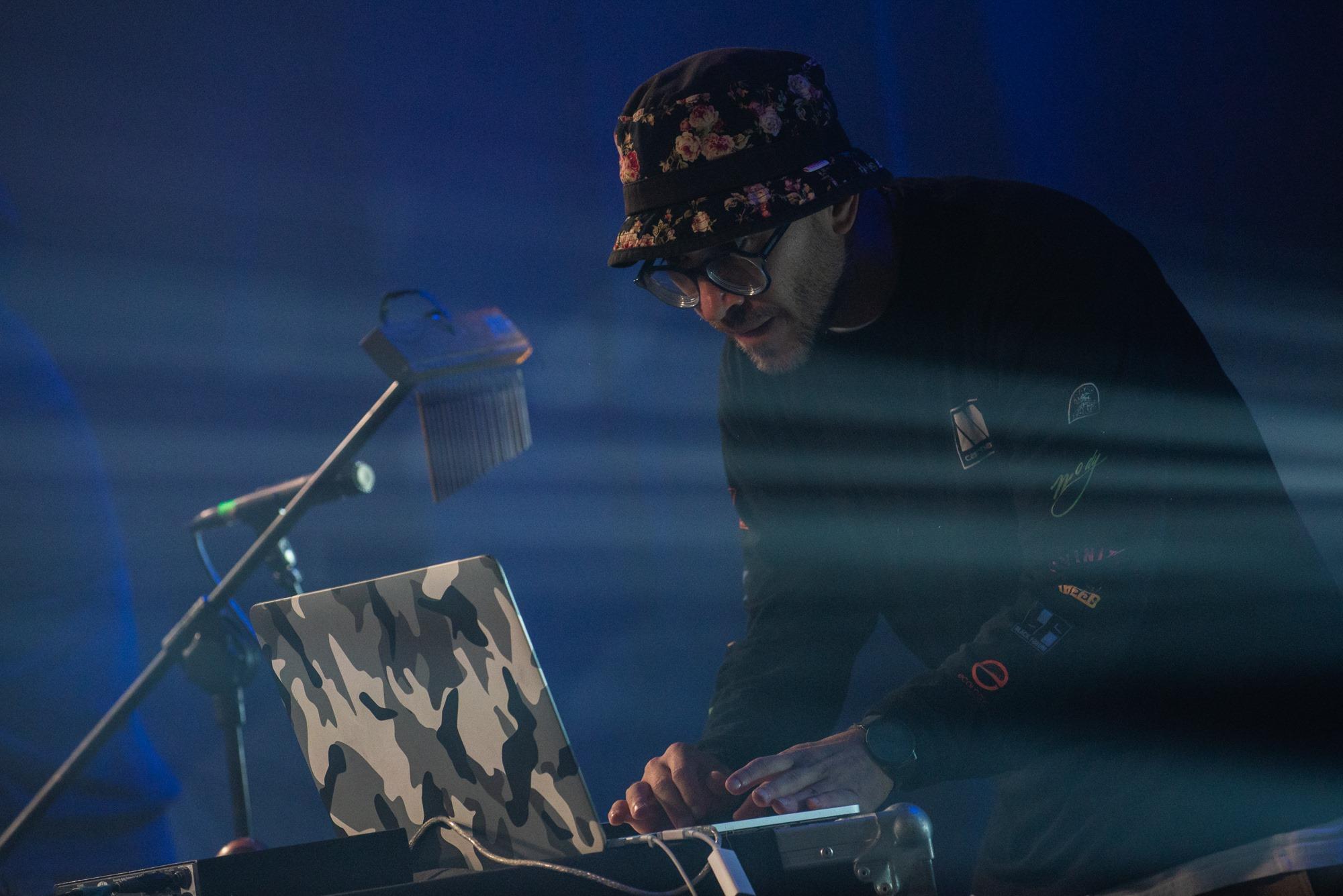 [Zdjęcie z koncertu. Mężczyzna w ciemnej czapce w kwiaty pochyla się nad laptopem w moro. Na nosie ma okulary. Oświetlony jest niebieskim światłem.]