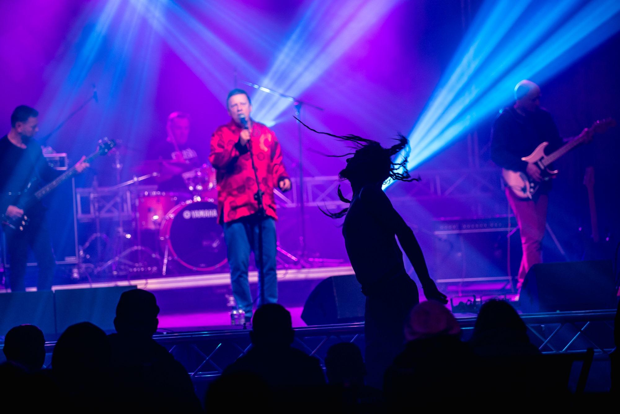 [Zdjęcie z koncertu zespołu Bielizna. Na pierwszym planie widać sylwetkę mężczyzny w dredach z krótką brodą. Mężczyzna znajduje się na widowni i skacze do góry. Wokół nigo widoczne są ciemne sylwetki innych osób z publiczności. W tle znajdują się członkowie zespołu Bielizna na scenie. Idąc od lewej - mężczyzna w ciemnej koszulce grający na gitarze, perkusista, piosenkarz w czerwonej koszuli przy mikrofonie na statywie oraz drugi gitarzysta w ciemnej bluzie.]