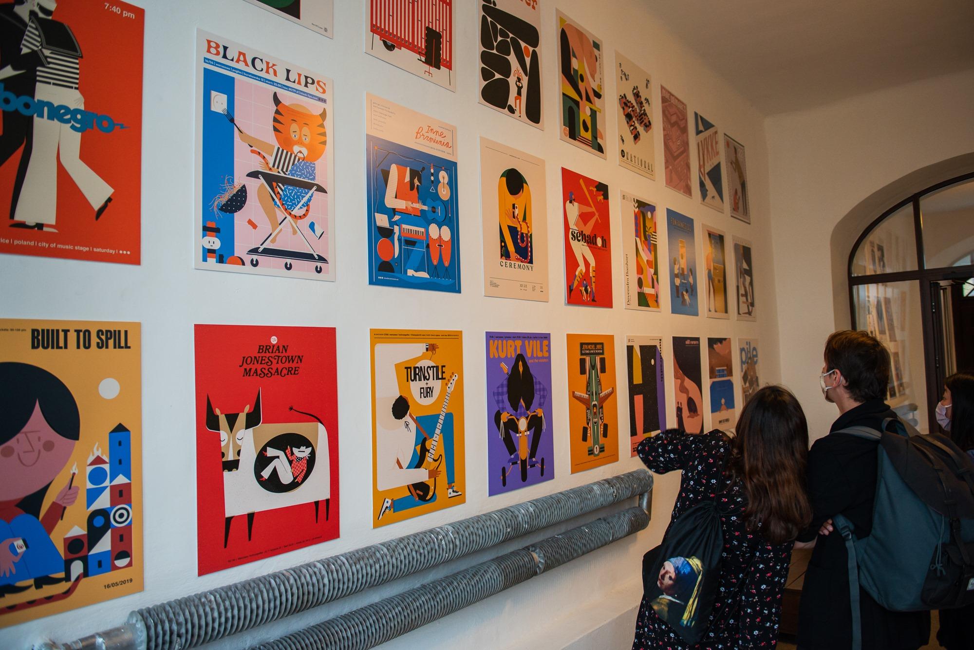 """[Zdjęcie przedstawia wystawę """"Plakat muzyczny"""" - Dawida Ryskiego. Widać sylwetki trzech osób - dwie kobiety i jednego mężczyznę w maseczkach na ustach i nosie, którzy wpatrują się w zawieszone na białej ścianie kolorowe plakaty.]"""