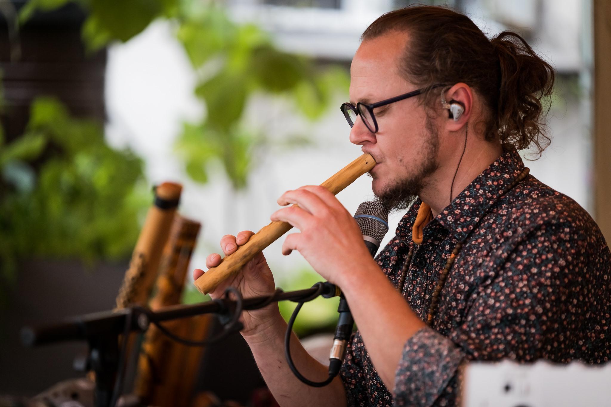 [Zdjęcie z warsztatu muzycznego T.Etno. Na zdjęciu Tomasz Drozdek gra na flecie. Przy twarzy artysta ma mikrofon umieszczony na statywie. Mężczyzna ma zamkniętę oczy. Widoczne na jego twarzy jest skupienie na grze na instrumencie.]