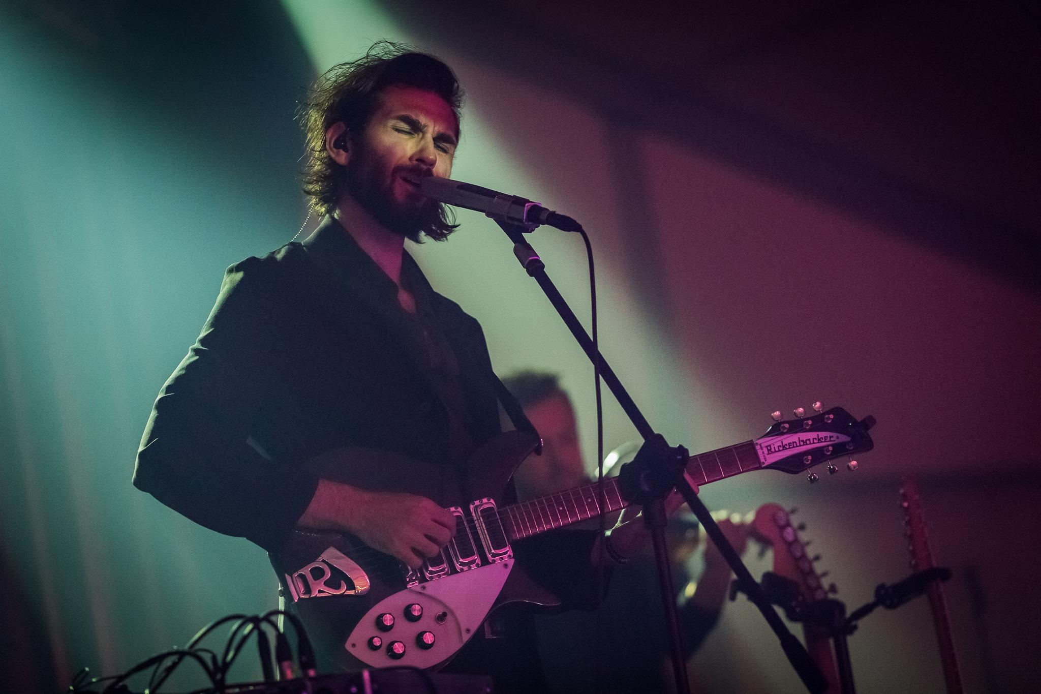 [Zdjęcie z koncertu Daniela Spanielaka. Mężczyzna śpiewa do mikrofonu umieszczonego na statywie i gra na gitarze. Ubrany jest w czarną koszulę oraz marynarkę. Ma dłuższe, ciemne włosy zaczesane do tyłu oraz delikatny ciemny zarost. W tle widać lekko rozmazaną sylwetkę mężczyzny grającego na skrzypcach. Oświetla ich niebiesko-różowe światło.]