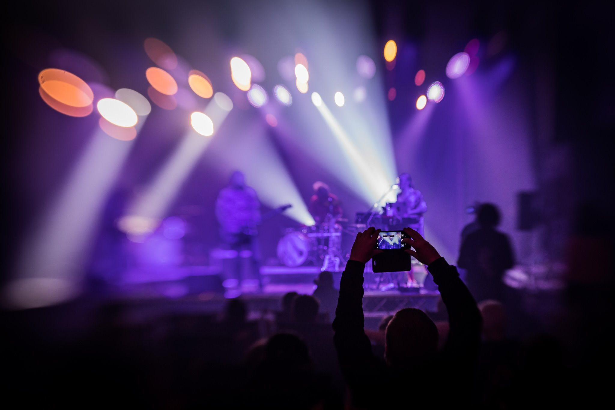 [Zdjęcie z koncertu. W centrum zdjęcia widać wyraźną sylwetkę mężczyzny stojącego między rozmytą publicznością. Mężczyzna ma podniesione do góry ręce i trzyma w dłoniach telefon. Nagrywa występujący na scenie zespół. W tle widać także lekko rozmyty grający na scenie zespół. Można wyróżnić sylwetki mężczyzn grających na gitarze, perkusji oraz keybordzie. Ośweitleni są fioletowym światłem.]