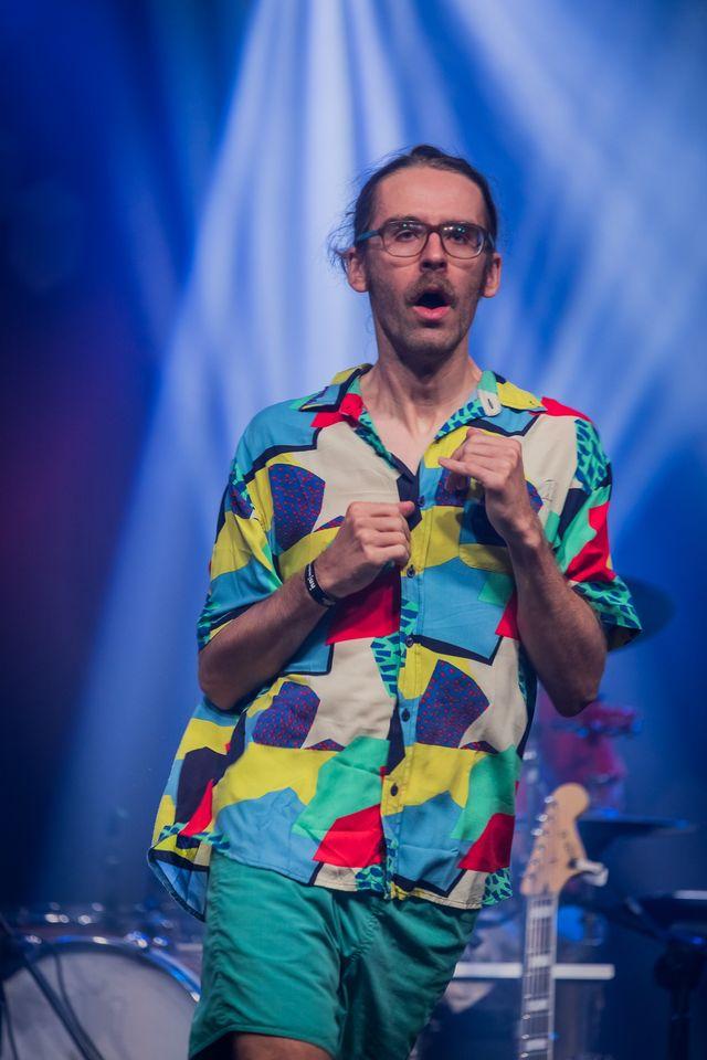 [Zdjęcie z koncertu Javva przedstawia śpiewającego mężczyznę w długich, związanych włosach i okularach. Mężczyzna ma kolorową koszulę i stoi na tle niebieskiego światła. Jego ręce są zgięte w łokciach przy ciele, a dłonie są złożone w piąstki.]