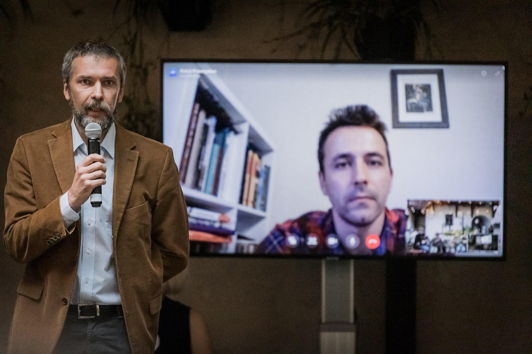 """[Zdjęcie ze spotkania autorskiego dotyczącego prezentacji książki Artema Czecha """"Dzielnica D"""" w ramach serii wydawniczej Wschodni Express. Na zdjęciu widoczny jest mężczyzna - Andrij Saweneć. Przemawia on do mikrofonu. Ma na sobie białą koszulę i brązową marynarkę. Za mężczyzną widoczny jest na ekranie Artem Czech, który bierze udział w spotkaniu on-line. Ubrany jest w koszulę w kratkę. Za jego plecami widoczna jest biała ściana, na której zawieszony jest obraz w ramce. Z lewej strony obrazu znajduje się także biały regał z półkami wypełnionymi książkami.]"""