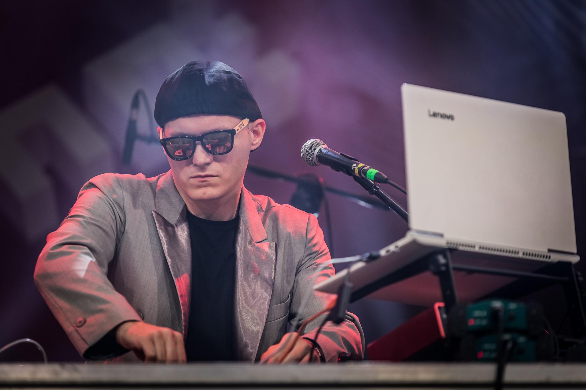 [Zdjęcie z koncertu przedstawia młodego mężczyznę tworzącego dźwięki na mikserze. Mężczyzna stoi przed mikrofonem umieszczonym na statywie, a przed sobą ma otwartego laptopa. Ubrany jest w jasną marynarkę i czarną koszulkę pod spodem.]