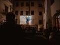 [Zdjęcie przedstawia kino w plenerze. Na ścianie kamienicy na zawieszonym ekranie wyświetlony jest kadr z filmu. Na patio przodem do ekranu siedzą na krzesłach ludzie oglądający film.]