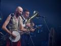 [Zdjęcie z koncertu zespołu Hańba. Na pierwszym planie znajduje się mężczyzna w jasnej koszuli i czerwonych spodniach śpiewający do mikrofonu i grający na Banjo. Na drugim planie mężczyzna grający na Tubie.]