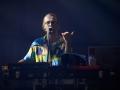 [Zdjęcie z koncertu zespołu Javva przedstawia mężczyznę w okularach i kolorowej koszuli śpiewającego przy mikrofonie i grającego na keyboardzie]
