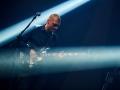 [Zdjęcie z koncertu przedstawia mężczyznę w koszuli stojącego przy statywie z mikrofonem, grającego na gitarze.]