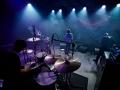 [Zdjęcie z koncertu z perspektywy kulis. Członkowie zespołu stoją tyłem do obiektywu aparatu. Trzech mężczyzn gra na gitarach, jeden mężczyzna gra na perkusji.]