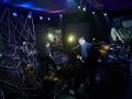 [Zdjęcie z wnętrza studia przygotowanego do koncertu. Scenografia zbudowana z aluminiowej kratownicy. Na zdjęciu członkowie zespółu - wokalista przy mikrofonie oraz mężczyźni grający na perkusji, saksofonie oraz keyboardzie.]