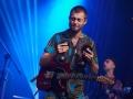 [Zdjęcie z koncertu Nubiyan Twist. Na tle niebieskiego oświetlenia widoczny jest gitarzysta w kolorowej koszuli, który trzyma w dłoniach kastaniety.]