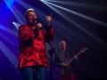 [Zdjęcie z koncertu zespołu Bielizna. Na pierwszym planie znajduje się wokalista w czerwonej koszuli śpiewajacy do mikrofonu. Na drugim planie znajduje się mężczyzna grający na gitarze elektrycznej.]