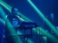 [Zdjęcie z koncertu zespołu MU. Na pierwszym planie znajduje się mężczyzna przy mikrofonie, grający na keyboardzie. W tle mężczyzna grająy na saksofonie.]
