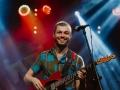 [Zdjęcie z koncertu Nubiyan Twist przedstawia młodego, uśmiechniętego mężczyznę w kolorowej koszuli. Mężczyzna stoi przed mikrofonem na statywie oraz gra na gitarze. W tle widoczne jest oświetlenie sceny w kolorze czerwonym oraz niebieskim.]