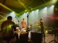 [Zdjęcie z koncertu wykonane za plecami występującego zespołu. Najbliżej mężczyzna grający na perkusji, dalej dwóch mężczyzn grających na gitarach. Pomiędzy nimi ustawione statywy z mikrofonami. Wszyscy ubrani w kolorowe koszule. Zielone oświetlenie sceny. W tle widać publiczość oświetloną w kolorze czerwieni.]