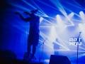[Zdjęcie z koncertu. Na pierwszym planie znajduje się mężczyzna w masce przypominającej z wyglądu szczura z wyciągniętymi rękami przed siebie. W tle widać sylwetkę drugiego mężczyzny śpiewającego do mikrofonu. Oświetlenie w kolorze niebieskim. Na drugim planie widoczny napis nazwy zespołu - Rat Kru]