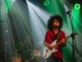 [Zdjęcie z koncertu Ayoub Houmanna & Nomads Moods. Na pierwszym planie mężczyzna w ciemnych włosach oraz czerwonej koszuli stoi przed mikrofonem na statywie i gra na gitarze. W tle perkusista. Oświetleni są zielonym i białym światłem.]
