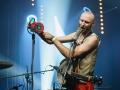 [Zdjęcie z koncertu Hańba. Mężczyzna ubrany w czerwone spodnie i jasną koszulę śpiewa do mikrofonu umieszczonego na statywie. Na ramieniu zawieszone ma na pasku banjo. W ręku trzyma syrenę alarmową i przykłada ją do drugiego mikrofonu na statywie. Oświetlenie jest niebieskie.]