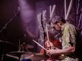 [Zdjęcie z koncertu Javva. Zdjęcie przedstawia mężczyznę w okularach i kolorowej koszuli grającego na perkusji. W rękach trzyma pałeczki. W stronę instrumentu skierowane są dwa mikrofony na statywach. W tle widać lekko rozmytą sylwetkę mężczyzny w pomarańczowej koszuli oraz fragment scenografii zbudowanej z aluminiowej kratownicy.]