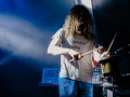 [Zdjęcie przedstawia mężczyznę grającego na bębnie. W dłoniach trzyma pałeczki. Jest ubrany w białą koszulkę z czarnym napisem i niebieskie spodnie. Ma długie, rozuszczone włosy. Za nim stoi instrument z klawiszami. Oświetlony jest niebieskim światłem.]