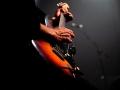 [Zdjęcie z koncertu. Zbliżenie na ręce mężczyzny grającego na gitarze. Na dłoni ułożonej na strunach widoczne żyły. Mężczyzna ma czarną koszulę z długim rękawem. Tło jest ciemne z przebijającym jasnym światłem.]