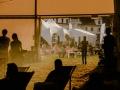 [Zdjęcie zrobione z perspektywy wyjścia z namiotu. Widok na ludzi siedzących na leżakach rozłożonych na trawie w obszarze Klubu Festiwalowego przed namiotem. Ludzie oświetleni są światłem słonecznym. Za nimi w tle widać białe namioty. Pod namiotem z którego zrobione jest zdjęcie widoczne są sylwetki osób siedzących lub stojących tyłem do wyjścia.]