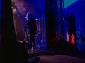 Zdjęcie z koncertu zronione z perspektywy kulis. Na scenie znajduje się kobieta grająca na keyboardzie. Za jej plecami znajduje się scenografia zbudowana z aluminiowej kratownicy. Za scenografią stoi mężczyzna nagrywający kamerą występ artystki. Na podłodze, za kulisami leżą czarne kable. Oświetlenie jest niebieskie.