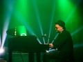 [Zdjęcie z koncertu przedstawia mężczyznę grającego na fortepianie. Obok fortepianu stoi mikrofon umieszczony na statywie. Mężczyzna ma okulary oraz czarny kapelusz na głowie. Ubrany jest w ciemną koszulę oraz spodnie. Oświetla  go zielone światło.]