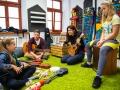 [Zdjęcie z warsztatu muzycznego dla dzieci. Na zdjęciu prowadzący zajęcia - młoda kobieta i mężczyzna oraz dwie uczestniczki warsztatu w wieku około 7 lat. Prowadzący oraz jedna z uczestniczek siedzą na zielonym dywanie i trzymają w ręku gitarę i ukulele. Jedna z uczestniczek siedzi na cajonie - instrumencie perkusyjnym. Pomiędzy nimi na dywanie rozłożone są różne instrumenty muzyczne takie jak ukulele, tamburyn, dzwonki, marakasy. Za nimi widać białą ścianę z dwoma oknami oraz czarnymi tablicami przytwierdzonymi do ściany. Wzdłóż jednej ze ścian ustawione są wycięte ze steropianu kształty budynków pomalowane na kolorowo.]