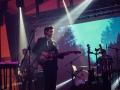 [Zdjęcie z koncertu Daniela Spanielaka. W centrum zdjęcia mężczyzna w ciemnych, dłuższych włosach i zaroście grający na gitarze. Ubrany jest w czarne spodnie, koszulę oraz marynarkę. Na przeciwko niego stoi statyw, na którym umieszczony jest mikrofon. Po lewej stronie artysty widać lekko rozmytą sylwetkę gitarzysty, natomiast po prawej stronie perkusisty. Ponad artystami widoczny jest fragment scenografii zbudowanej z aluminiowej kratownicy. W tle poniżej wyświetlona jest projekcja na której widać fragment wieczornego nieba pomiędzy wierzchołkami drzew.]