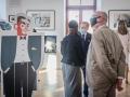 """[Zdjęcie przedstawia wystawę """"Bauhaus - szkoła nie tylko dla dorosłych"""". Na pierwszym planie Dyrektor Warsztatów Kultury w Lublinie - Grzegorz Rzepecki. Na ustach i nosie ma założoną czarną maseczkę. Ręce trzyma złożone z tyłu ciała. Mężczyzna patrzy z ciekawością na jeden z elementów wystawy - eksponat przedstawiający grafikę eleganckiego mężczyzny w garniturze stojącego z rękami w kieszeniach.  Na dalszym planie widoczny jest Dyrektor Narodowego Centrum Kultury - dr hab. Rafał Wiśniewski, prof. ucz. ubrany w niebieski garnitur. Mężczyzna patrzy z zaciekawieniem na elementy wystawy. W sali są także dwie dwie kobiety oglądające zawieszone na białej ścianie ilustracje w ramkach. Stoją tyłem do obiektywu aparatu i nie widać ich twarzy. Jedna z nich ubrana jest w ciemną, długą sukienkę, kurtkę jeansową i czarną kaszkietkę. Ma rozpuszczone, ciemne włosy i czarną kaszkietkę na głowie. Druga kobieta ubrana jest w jasną sukienkę, a na ramieniu zawieszoną ma białą torebkę. Jej włosy są rozpuszczone w kolorze blond.]"""