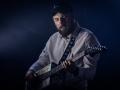[Zdjęcie z koncertu przedstawia mężczyznę grającego na gitarze. Ubrany jest w białą koszulę oraz czarną czapkę z daszkiem. W tle oświetlenie niebieskie.]