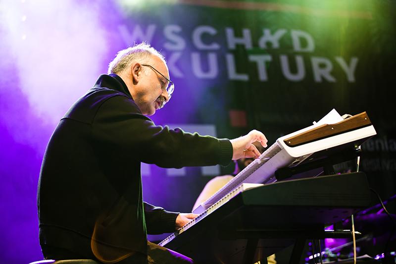 """Iriao, fot. Robert Pranagal [Starszy mężczyzna grający na instrumencie klawiszowym w zespole Iriao pośród scenicznych świateł. W tle napis """"Wschód Kultury"""".]"""