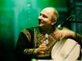 Iriao, fot. Robert Pranagal [Uśmiechnięty mężczyzna w średnim wieku w haftowanej szacie z instrumentem w ręku siedzi na scenie. W tle zielone światło reflektorów]