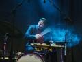 [Na zdjęciu widać perkusistę zespołu, podczas grającego koncertu. Światło na sali jest chłodne, niebieskie.]
