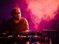Soft Eject, fot. Robert Pranagal [Fioletowo-różowe światło sceny. Mężczyzna w ciemnej koszulki i okularach tworzy muzykę nachylony nad konsoletą.]