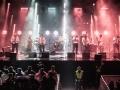 fot. Robert Grablewski [Duża grupa muzyków na rozświetlonej reflektorami scenie. Na scenie wokalistka, sekcja dęta, gitarzysta i perkusjonista]