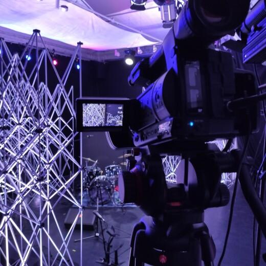 Zdjęcie z wnętrza studia przygotowanego do koncertu. Na pierwszym planie włączona kamera skierowana w stronę stanowiska perkusisty i scenografii zbudowanej z aluminiowej kratownicy.