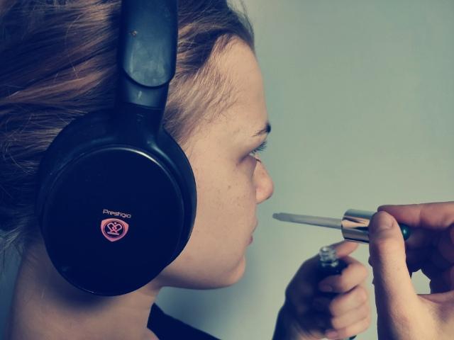 Zdjęcie młodej dziewczyny o jasnych włosach w słuchawkach na uszach. Dziewczyna wącha perfumy ze szklanej pipetki.