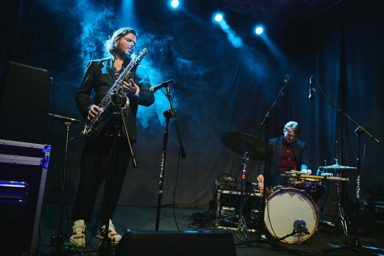 Zdjęcie dwóch muzyków formacji Malediwy podczas koncertu. Jeden z nich gra na saksofonie, drugi na perkusji.