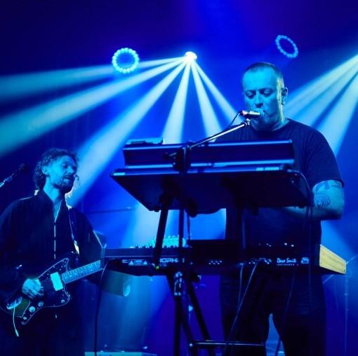 Zdjęcie z koncertu formacji MU. Na pierwszym planie Tymon Tymański grający na keybordzie, na drugim, gitarzysta elektryczny. Całość skąpana w błękitnym świetle reflektorów.